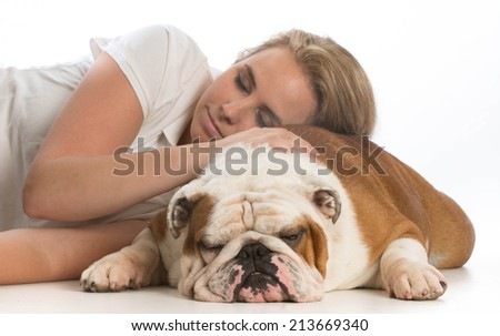 woman resting her head on her english bulldog on white background