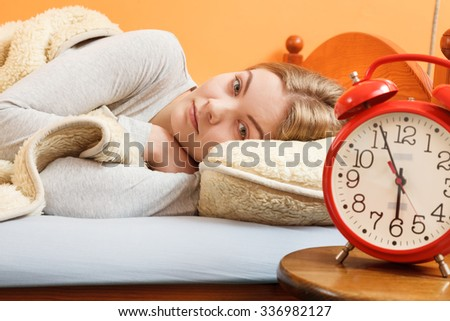 Woman resting in bed under blanket with set alarm clock. Girl relaxing napping.