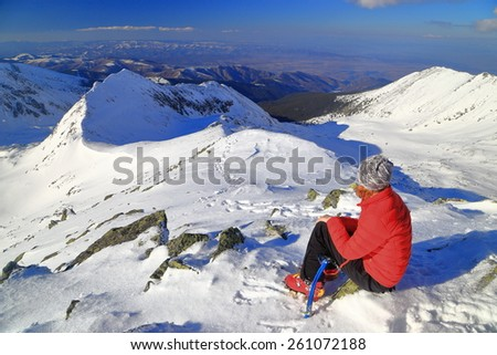 Woman resting on the mountain top in sunny winter day - stock photo