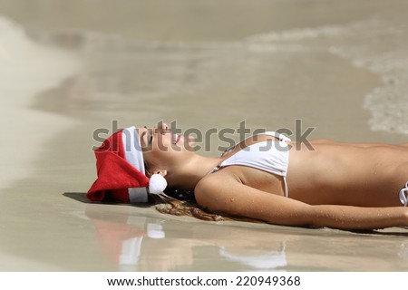 Woman resting on the sand of the beach relaxing on christmas holidays - stock photo