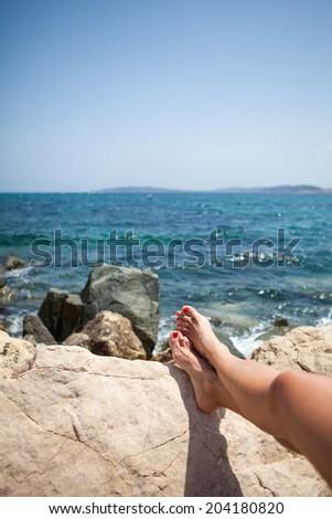Woman resting over the sea, rocky sea shore - stock photo