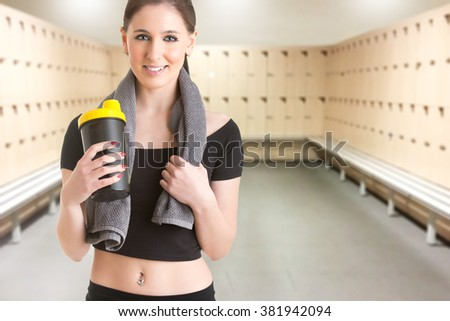 Woman resting with a towel around her neck after a fitness workout, in a gym - stock photo