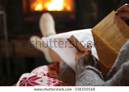 Woman resting with book near fireplace - stock photo
