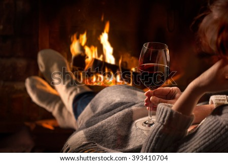 Woman resting with glass of red wine near fireplace - stock photo