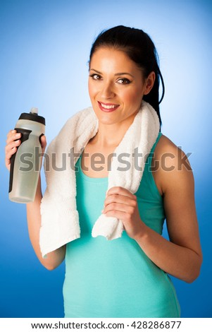 Woman rests after fitness workout with towel around her neck drinking water over blue background