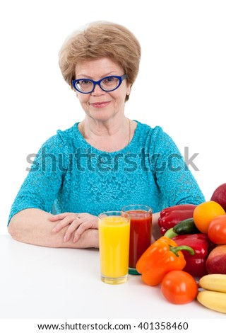Woman retirement age with tomato and orange juice in glasses sits at table with fruits and vegetables, isolated on white background - stock photo