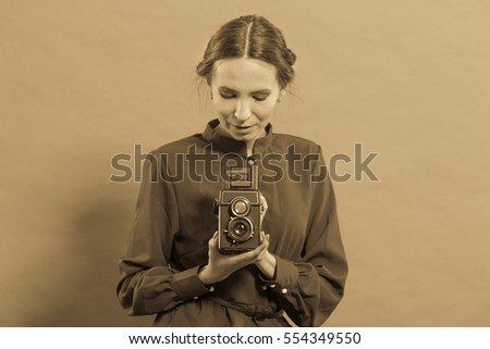 Woman retro style long dark gown taking picture with old camera, vintage photo