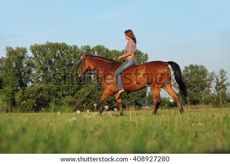 Woman ride bareback horse in a evening field - stock photo