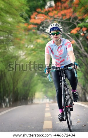 Woman ride bike in speedy on countryside with tree tunnel, healthy lifestyle concept and sport motivation idea - stock photo