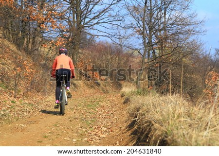 Woman rides a bike on dirt road in sunny day