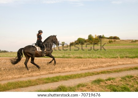 Woman rides at a gallop across the field. - stock photo
