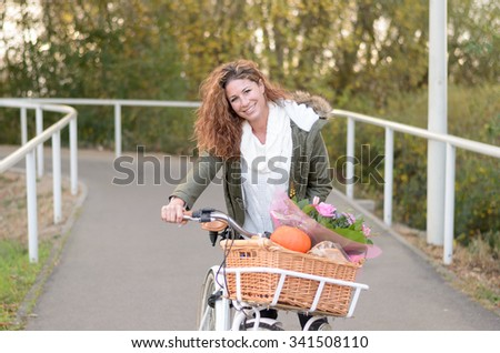 Woman riding a bicycle and has its purchases in the basket, while smiling in the camera