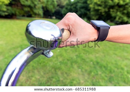 Woman riding a bike with a smartwatch heart rate monitor. Smart watch concept. Close-up smart watch on arm women to ride a bicycle. Woman is using smart watch during her workout. Smart watch concept.