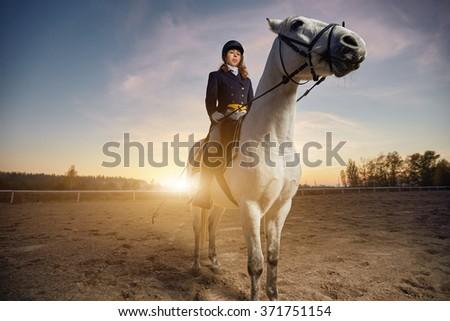 Woman riding a horse - stock photo