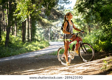 Woman riding a mountain bike in the forest. - stock photo