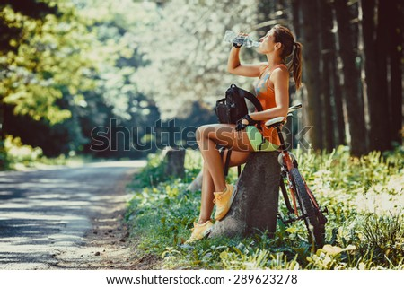 Woman riding a mountain bike in the forest.She  resting ,making pause. - stock photo