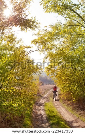 Woman riding a mountain bike on a forest road  - stock photo