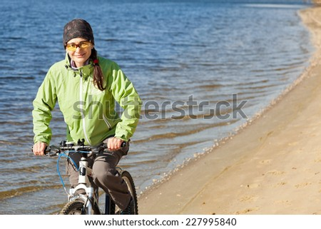 Woman riding a mountain bike on a river shoreline, looking at the camera. - stock photo