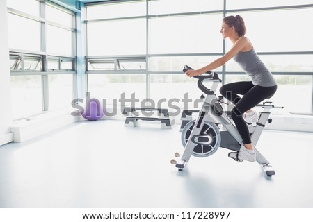 Woman riding an exercise bike in gym