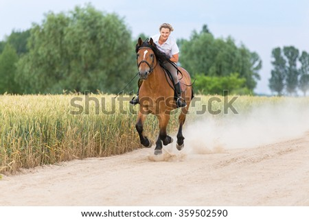 Woman riding bay horse in summer meadow. - stock photo