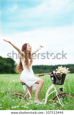 Woman riding bicycle in wildflower field - stock photo