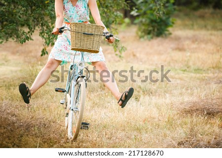 Woman riding bicycle with her legs in the air. Summer fun  - stock photo
