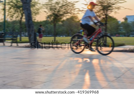woman riding bicycles on a city park street ,Intentional motion blur - stock photo