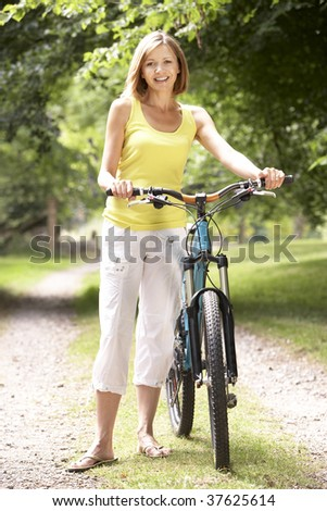 Woman riding bike in countryside - stock photo