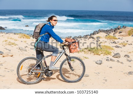Woman riding bike on a beach by the water - stock photo