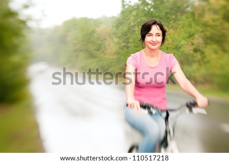 Woman riding bike smiling on the rainy forest road. Lensbaby effect - stock photo