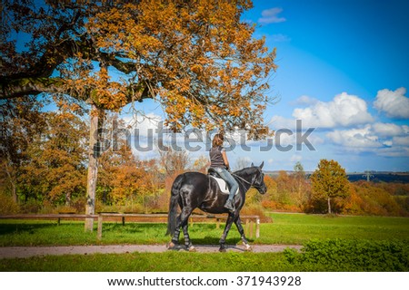 Woman riding horse  Landscape with a woman riding a beautiful black horse on an autumn sunny day. - stock photo