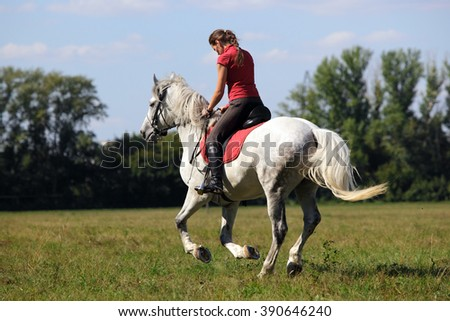 Woman riding horseback summer fields