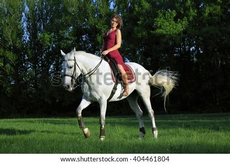 Woman riding horseback through evening forest glide - stock photo