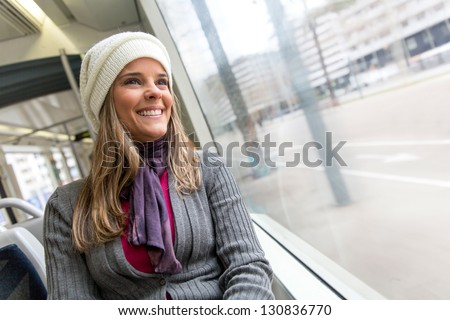 Woman riding in a bus and looking happy - stock photo