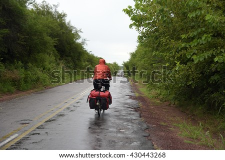 Woman riding in a raining day with a fully loaded folding bicycle in a small road 21,Urugua