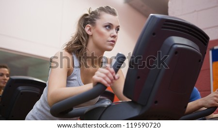Woman riding in a spinning class in gym - stock photo