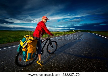 Woman riding loaded bicycle on the wet asphalt road with clouds on the background - stock photo