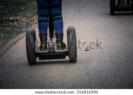 Woman riding on a Segway in the park - stock photo