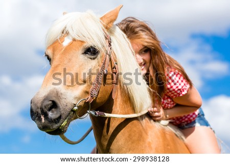 Woman riding on horse in summer meadow - stock photo