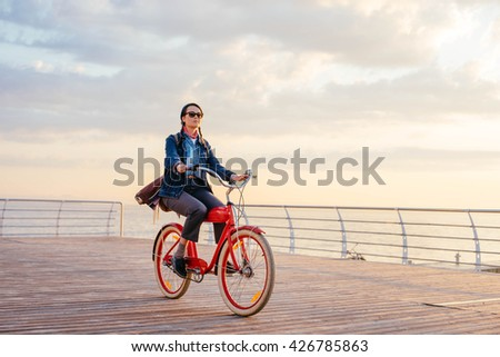 woman riding red vintage bicycle on seaside during sunset or sunrise