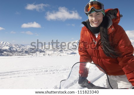 Woman riding snowmobile on a sunny day - stock photo