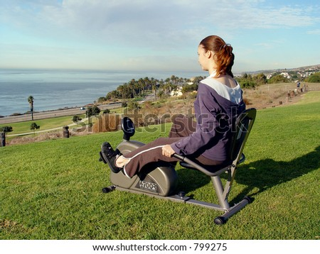 Woman riding / spinning on recumbent bike at sea Cliff! - stock photo