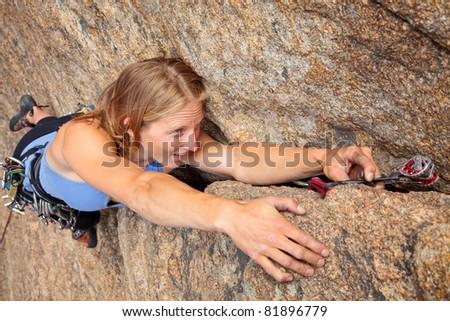 Woman rock climber placing piece of gear - stock photo