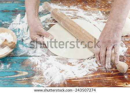 Woman rolling dough using rolling pin.   Woman kneading, baking cookies, pizza or bread  - stock photo