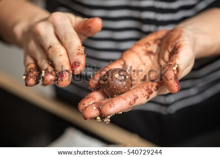 Woman rolling homemade chocolate truffles in her hands