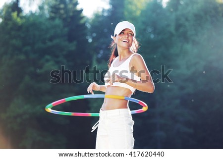 Woman rotates hula hoop outdoors in park - stock photo