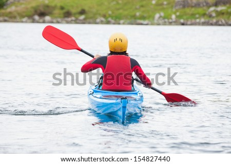 Woman rowing in a kayak in a cold lake - stock photo