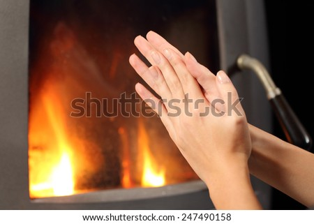 Woman rubbing hands and heating in front a fire place at home in winter - stock photo