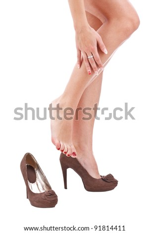 woman rubbing her legs over white background - stock photo