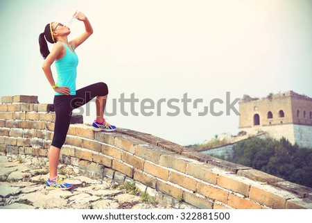 woman runner athlete drinking water after run on chinese great wall.   - stock photo